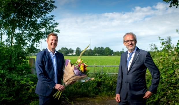 Wethouder Jouke Spoelstra (links) met bloemen voor Ulbe Bijlsma van Stertil. Op de achtergrond het bewuste terrein.