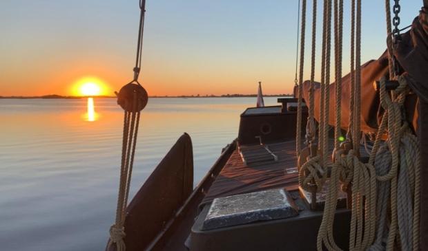 Varen bij zonsondergang met skûtsje De Rot.