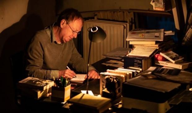 Levi Weemoedt aan het werk, met pen en papier, op de ouderwetse manier.