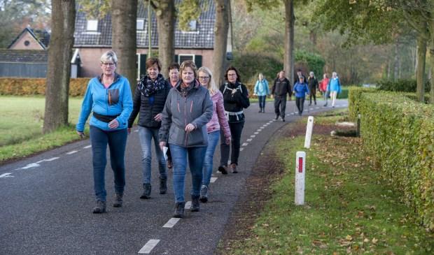 De eerste wandelaars passeren de Vosstraat in Oeken. Foto: Marion Verhaaf
