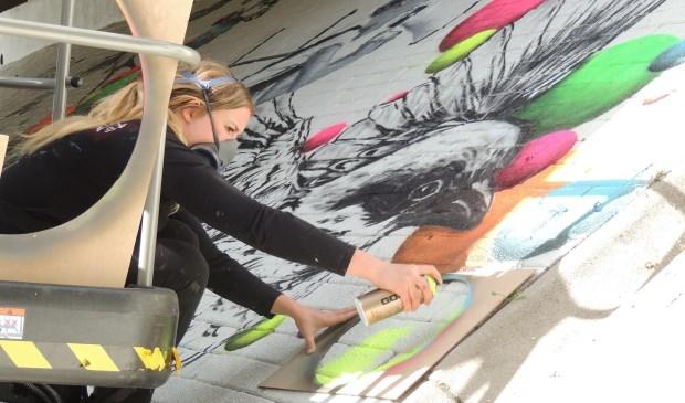 Street-art kunstenares Rosalie de Graaf aan het werk.