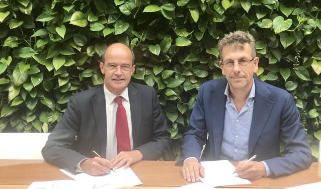 Burgemeester Alex van Hedel en directeur Marco de Wilde ondertekenen de koopovereenkomst.