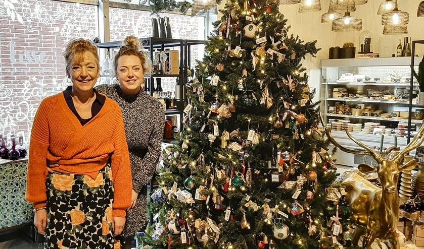 Esmee en Ivonne Beumkes bij een prachtig versierde kerstboom in Lisse, de delicatessenbank. Foto: Marion Verhaaf