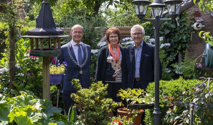 Het bruidspaar met burgemeester Van Hedel in hun prachtige tuin. Foto: Marion Verhaaf