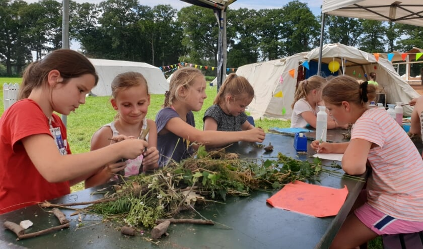 Kinderen bouwen een stationshal met materialen uit het bos.