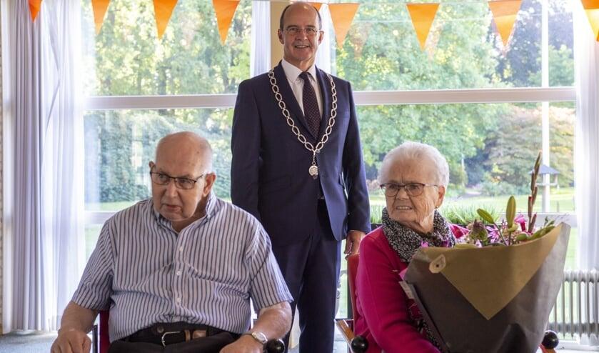Hendrik (84jr) en Dinie (85jr) Draaijer-Schotpoort met burgemeester Van Hedel op gepaste afstand. Foto: Marion Verhaaf