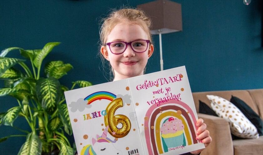 <p>Nikki opent op haar 6e verjaardag een kaart met muziek en ballon die de bezorger voor de deur zette. Foto: Marion Verhaaf</p>