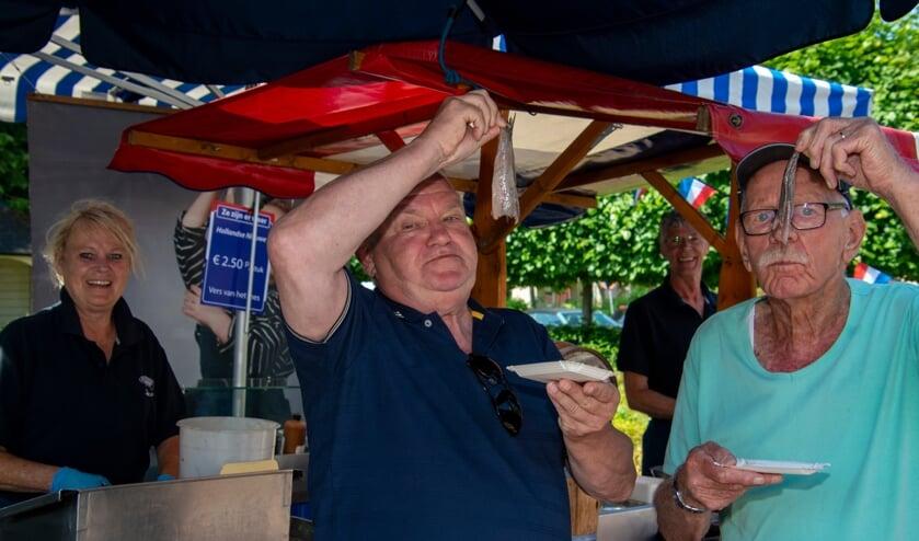 Henk Rozie en Jan Verweij genieten van hun haring. Foto: Marion Verhaaf