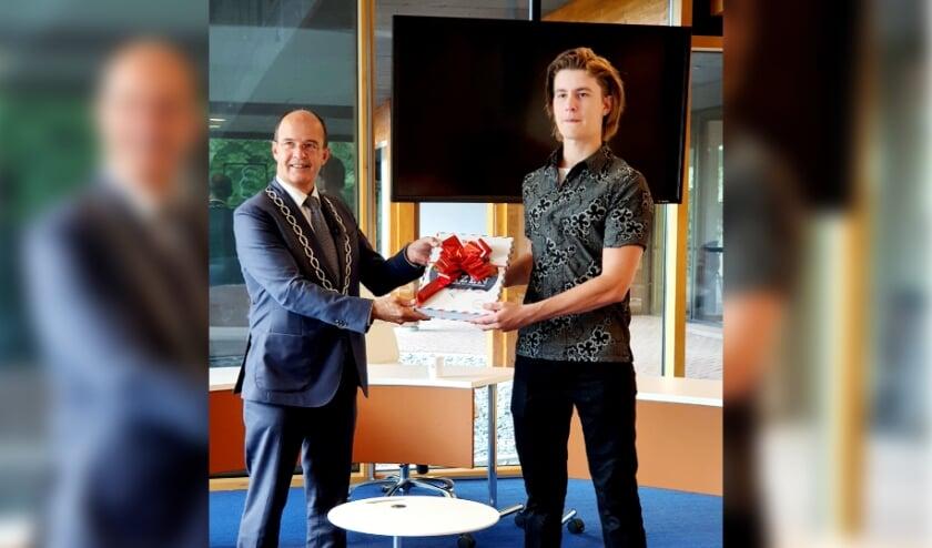 <p>Burgemeester van Hedel eert Rijk met cadeau.</p>