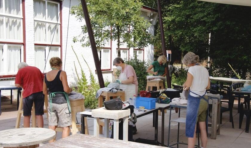 Beeldhouwen in de tuin van de KWA. (foto: Gerda Hendriks)