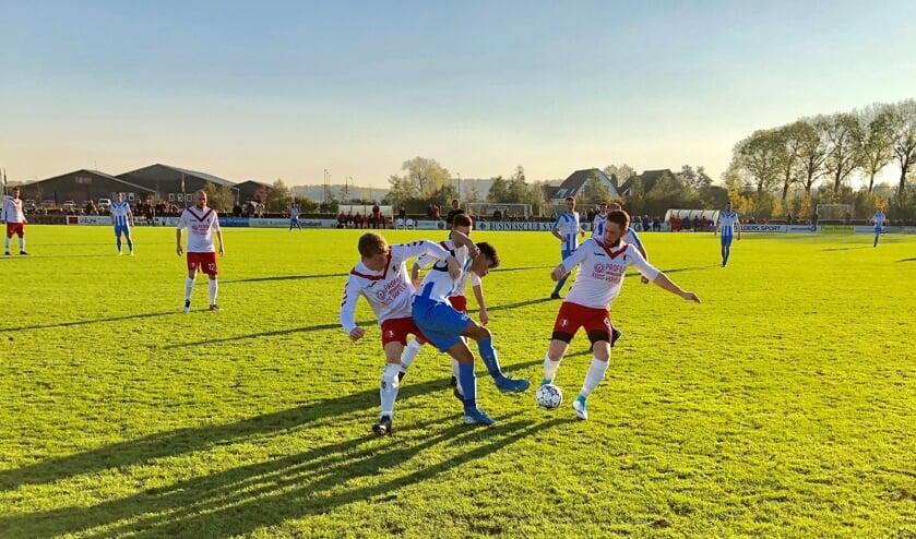 Arnhemse Boys (blauwe broek) in de greep van en bij RKSV Driel. Laatstgenoemde won de derby en kelderkraker van 3D West met liefst 6-1.