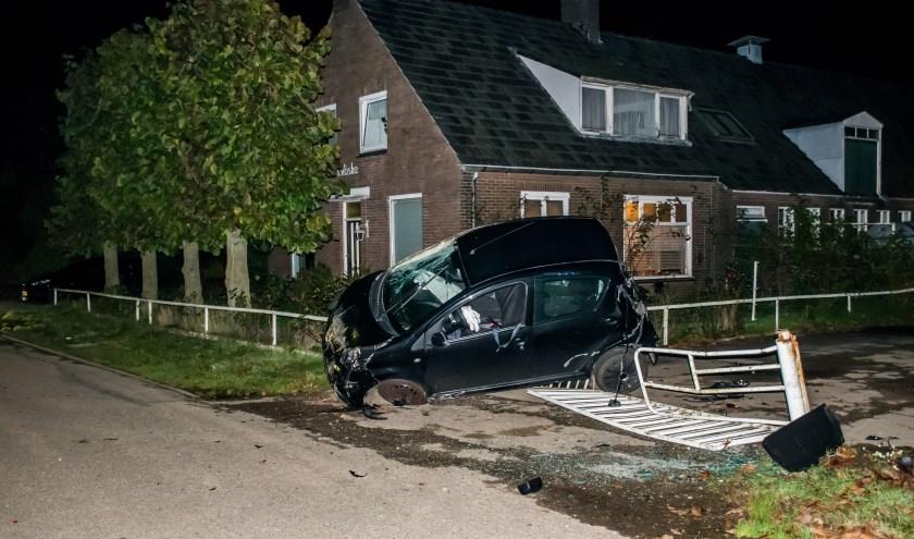 Auto op zijn kant tegen hekwerk. (foto: Waldie Rutten)