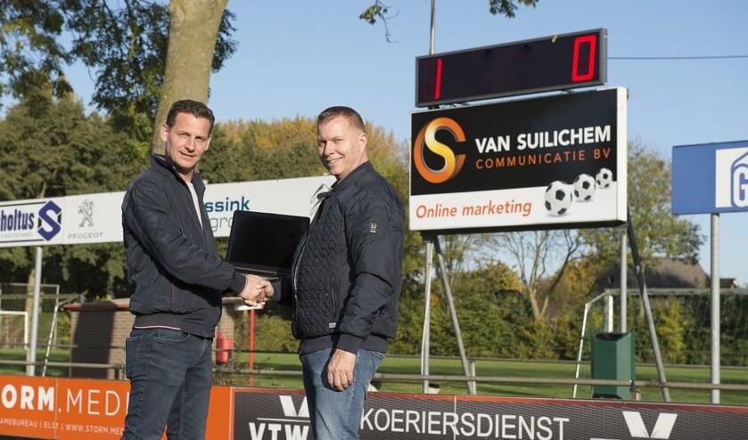 Cor van Suilichem en Dirko Hendriksen voor het nieuwe scorebord van VV Dodewaard.(foto: Thomas van Beek)
