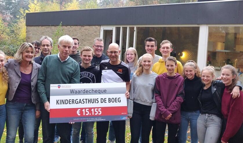 Leerlingen van het Montessori College bij de overhandiging van de cheque aan voorzitter Sjaak Thijssen van De Boeg; rechts Wilbert Lamers docent lichamelijke opvoeding aan het Montessori College