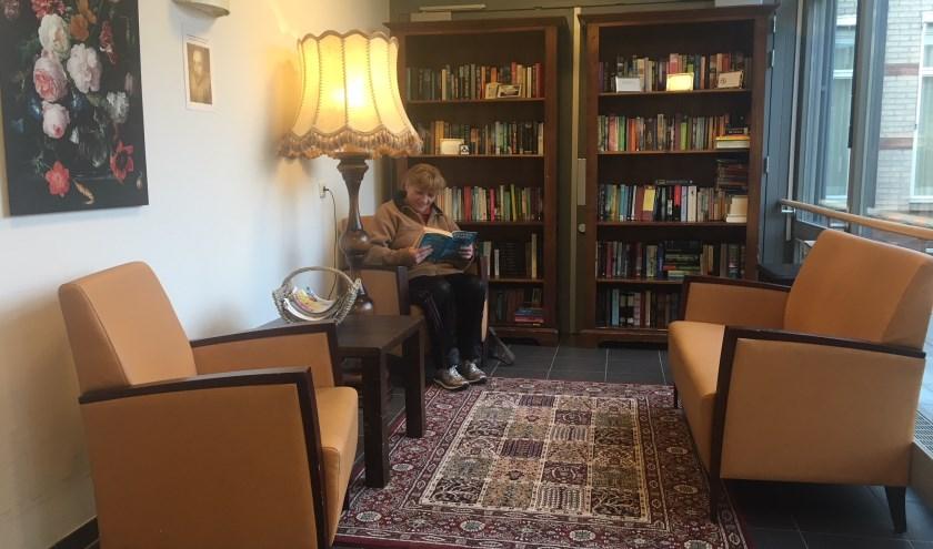 Een bezoekster van De Lingehof, die een boek leest in ons boeken-ruil-kast hoekje. (foto: Bianca)