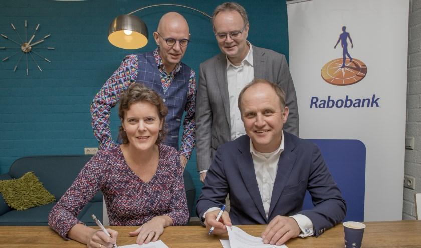 Onder het toeziend oog van economiedocent Ben Nijmeijer (links) en directielid  Ben van den Anker van het Candea College in Duiven tekenen Esther van Kraaij (Rabobank Arnhem en Omstreken) en Niek den Tex (Scholenstrijd) de overeenkomst. (foto: Sjoerd Geurts)