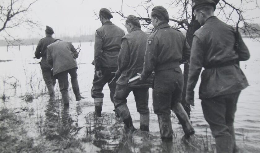 Britse soldaten waden door het overstroomde niemandsland. (foto: Ferdinand van Hemmen)