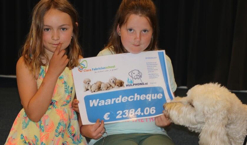 Marieke en Wendy overhandigen de waardecheque aan Nora, hulphond van Mirjam, ambassadeur van Stichting Hulphond. (foto: Moss Tijssens)