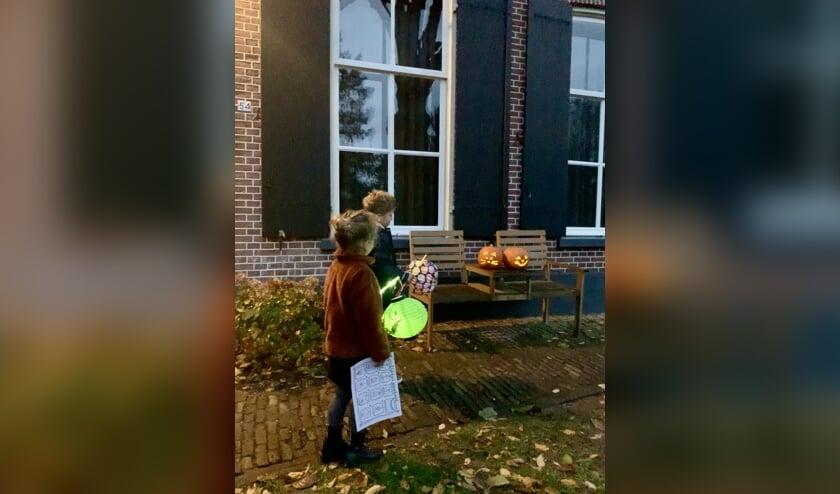 Twee kinderen alvast een rondje door de wijk lopen op zoek naar lichtjes met de zoekkaart in de hand.