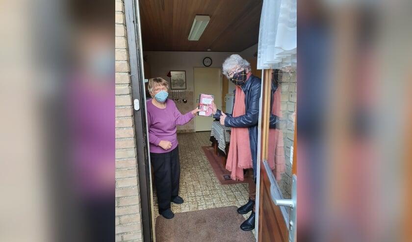 <p>Marion Schouten, vrijwilligster Huiskamer van Elst overhandigt het kookboek aan een blije Ans Schoonderbeek. (foto: Ton Schouten)</p>