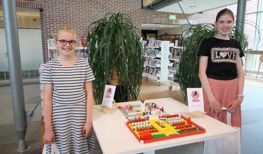 Emma en Johanna Hulsman bij hun Lego-creatie van de Grebbeberg. (foto: Marco Diepeveen)