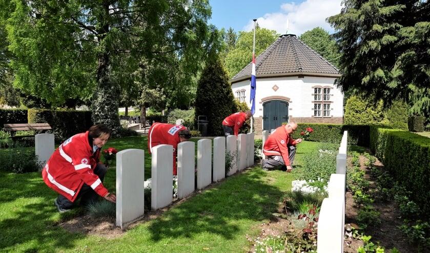 Foto's van de vrijwilligers die bloemen leggen op de algemene begraafplaats aan de Achterbergsestraatweg in Rhenen.