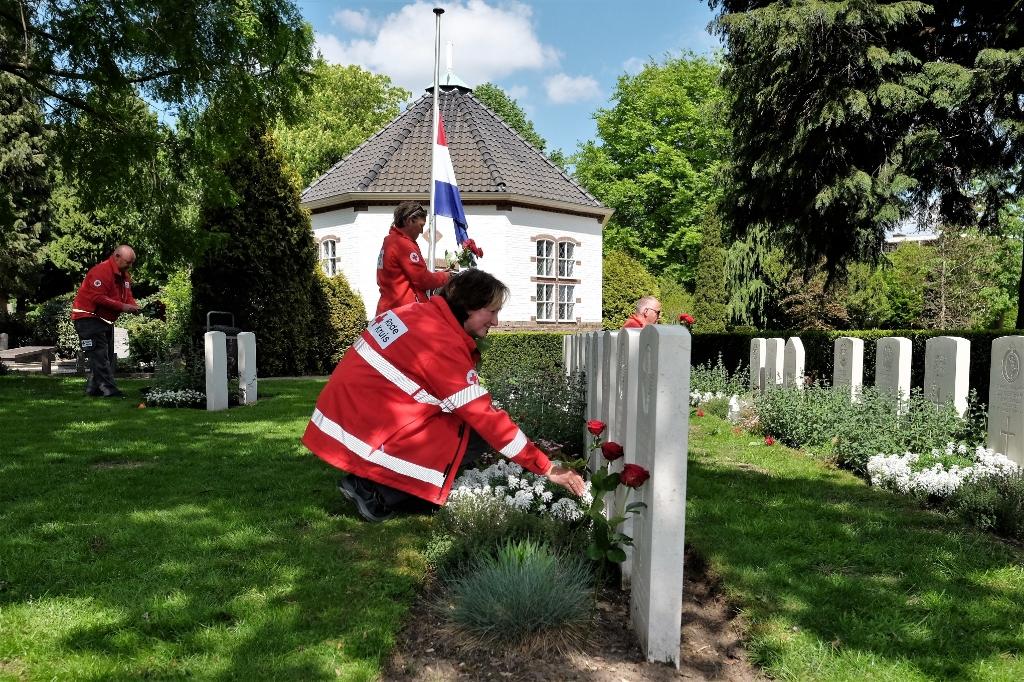 Foto's van de vrijwilligers die bloemen leggen op de algemene begraafplaats aan de Achterbergsestraatweg in Rhenen. Foto:  © Hét Gemeentenieuws