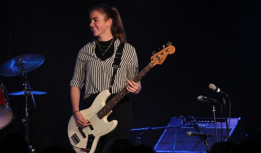 Linn spelend op haar basgitaar tijdens een optreden met haar band op een van de muziekavonden die de school regelmatig organiseert. (foto: Veerle Karsdorp)