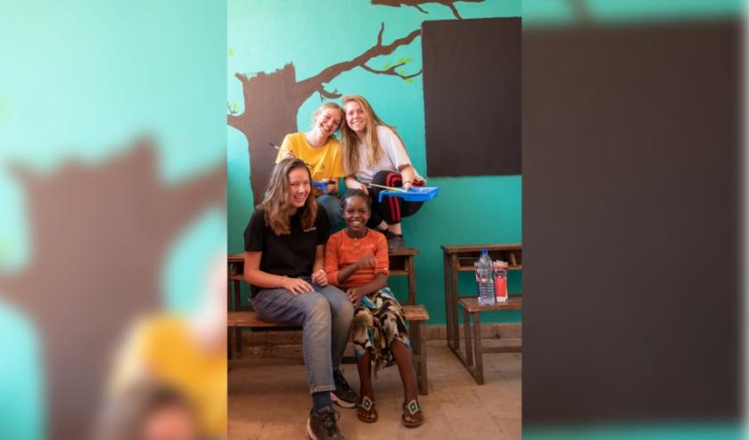 Jill Wijnbergen (zittend), pauzeert even tijdens het klussen en heeft de grootste lol met de dochter van een van de leraressen. (foto: Jan van den Heuij)