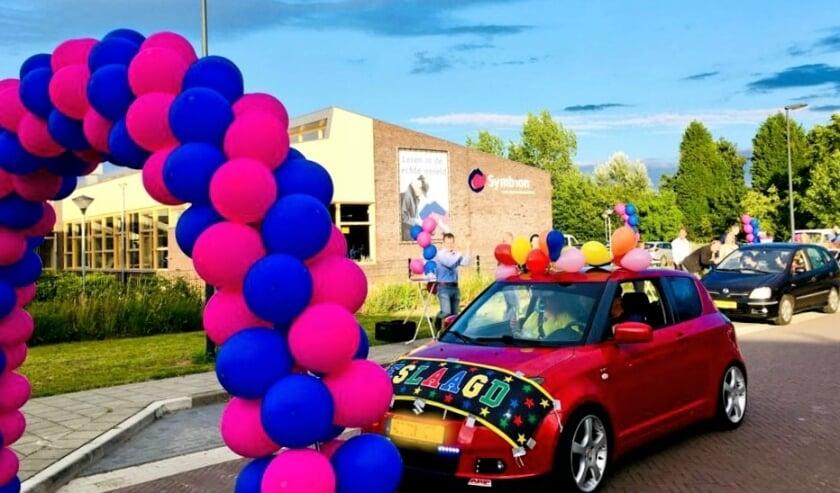 De leerlingen namen in hun auto hun diploma in ontvangst.
