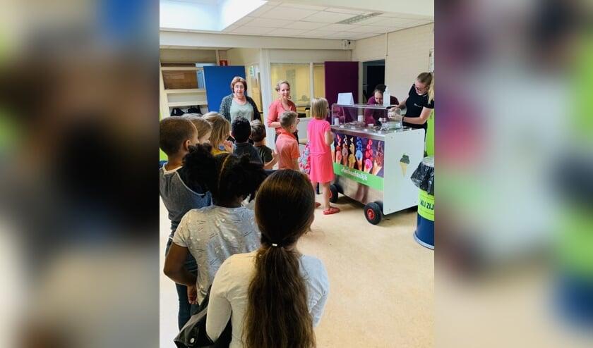 Kinderen staan in de rij voor een bekertje ijs. (Moeder Latifa Poulisse, Lid OR Okkernoot)