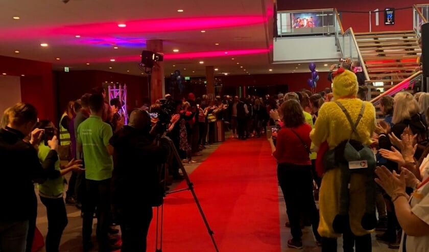 Beroepsbeoefenaren juichen de leerlingen toe die op de rode loper binnenkomen. (foto: Floor Thijsen)