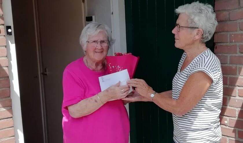 Zonnebloemvrijwilliger reikt plantje uit aan gast mevrouw W. van Hasselaar. (foto: Reinolda de Bruin)