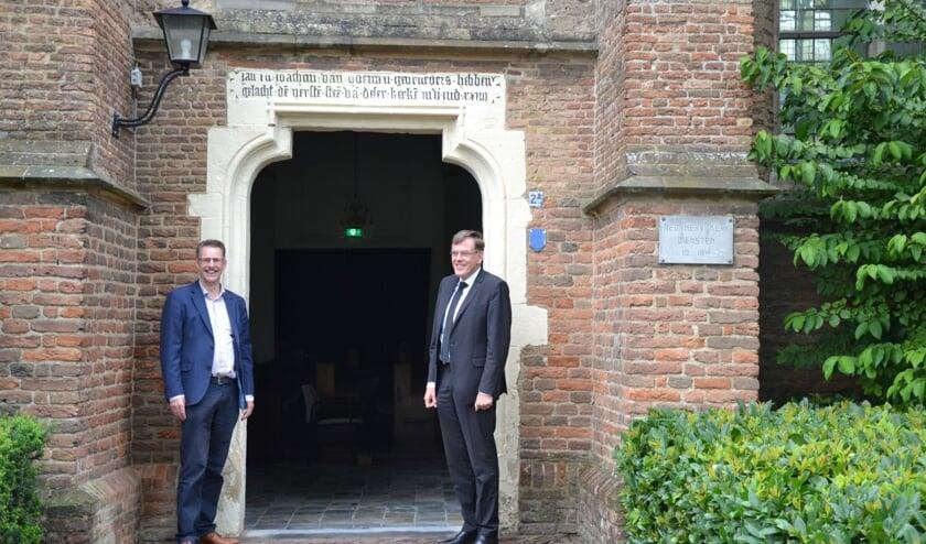 Bij de ingang van de kerk. Rechts staat de predikant van de gemeente, dominee R. van de Kamp en links Bart van Kleef, voorzitter van de evangelisatiecommissie. (foto: Nienke Heenck/HHK)