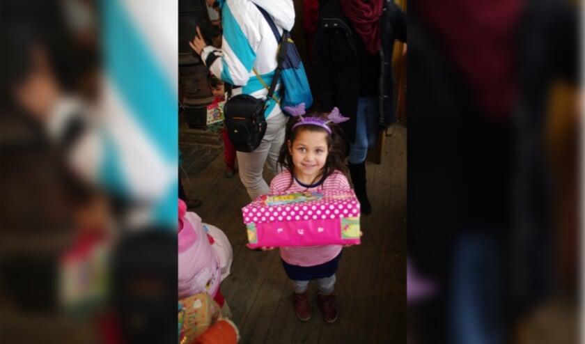 <p>Roma kind met net gekregen schoenendoos met speelgoed. (foto: A de Wit)</p>