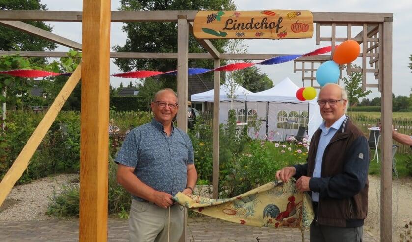 <p>Vrijwilligers Ton de Jong en Bart Kleijer onthullen de naam van de moestuin. (foto: G. Verboom)</p>
