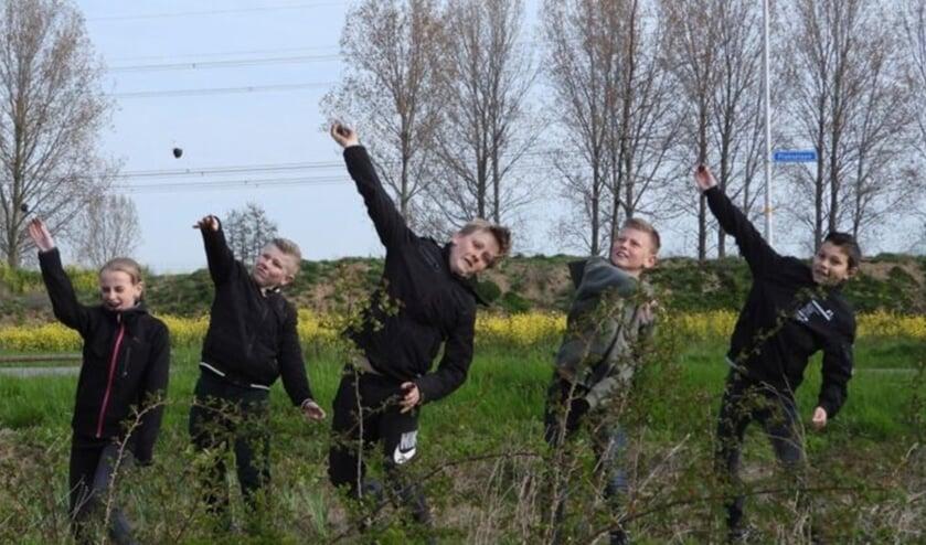 <p>Basisschoolleerlingen gooien biodiversiteitsbommen op het Plaksche Veld. (foto: Rietje van Dalen SLN)</p>