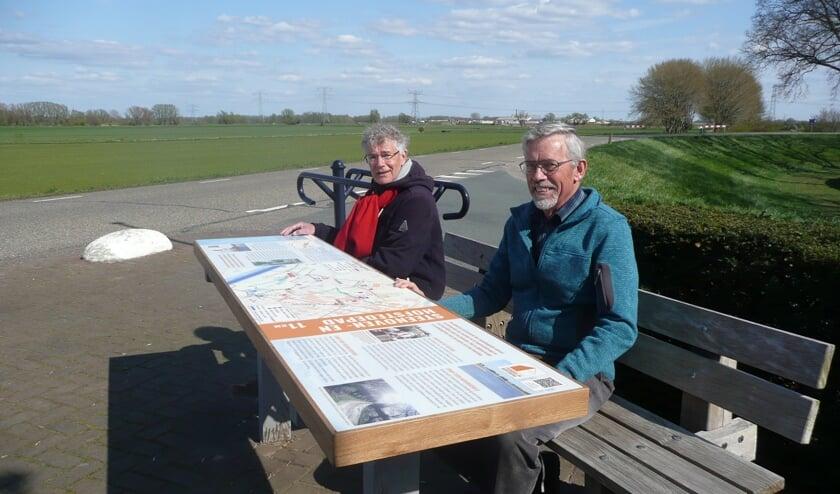Geert Bouwman en Geert Tijssen (r) van de werkgroep Ommetje Steenoven en Hofstedepad zitten bij het startpaneel van de wandelroute dat tevens dienst doet als tafel. De overige werkgroepleden staan vanwege de coronamaatregelen niet op de foto.