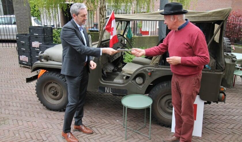 <p>Roeland Janssen (met hoed) overhandigt Rhenens burgemeester Hans van der Pas het fietsrouteboekje. (foto: Marco Diepeveen)</p>