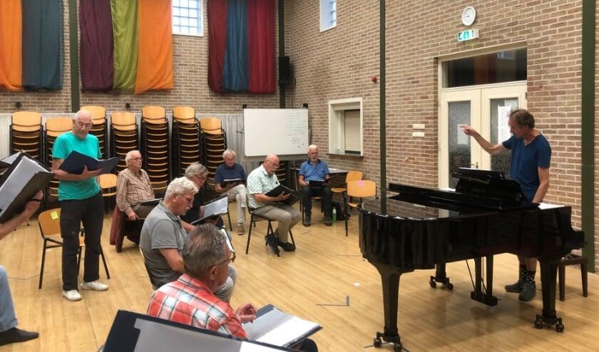 <p>De dirigent en een aantal koorleden op de eerste repetitie na de coronamaatregelen. (foto: Menno Tillema)</p>
