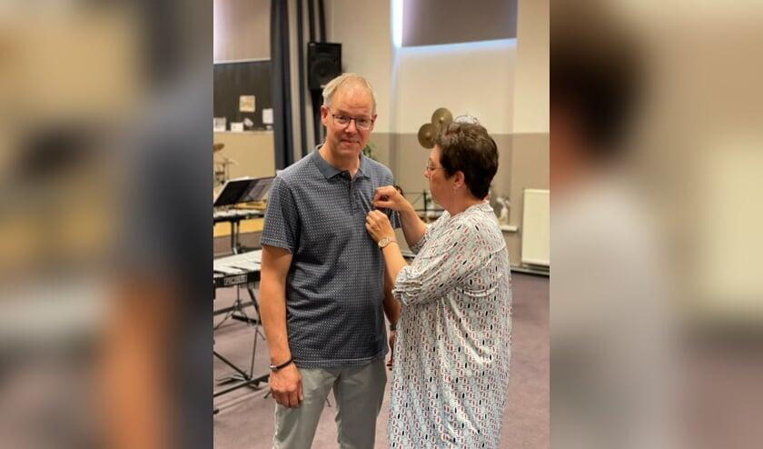 <p>Dirk van Ewijk krijgt versierselen opgespeld door zijn vrouw Gea. (foto: Jeroen van IJmeren)</p>