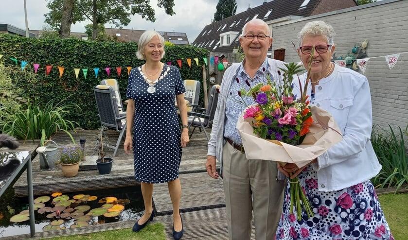 <p>Burgemeester Mittelndorff feliciteert het diamanten paar met een fraai boeket bloemen en een ingelijste trouwacte. (foto: Joop Verstraaten)</p>