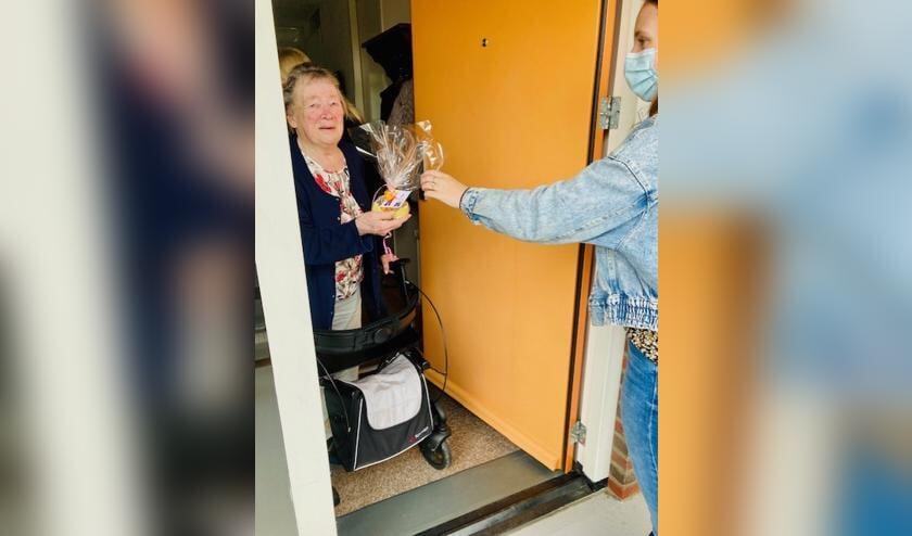 <p>Leerling biedt buurvrouw een attentie aan. (foto: Yvon van Oijen)</p>